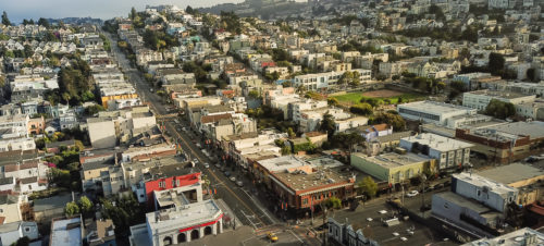 Panorama aerial view Eureka Valley neighborhood with rolling hills cityscape, typical Victorian houses. Castro District is synonymous with gay culture, tightly packed residential homes summer foggy